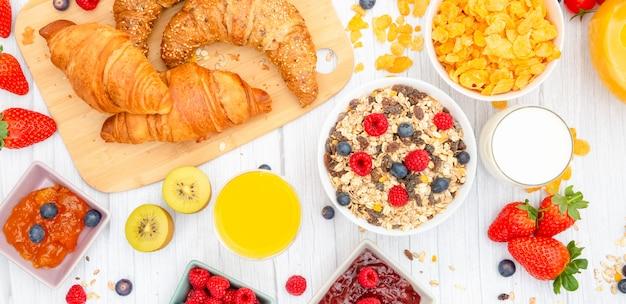 Rano śniadanie z maślanymi rogalikami i płatkami kukurydzianymi, pełnymi ziarnami i rodzynkami.