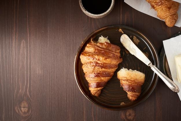 Rano śniadanie z rogalikiem i plasterkiem na talerzu, filiżance kawy, dżemu i masłem.