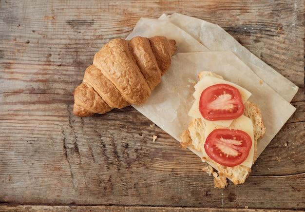 Rano śniadanie z rogalików. dwa rogaliki na drewnianym tle. obfity rogalik z pomidorem i serem. zbliżenie z kopią miejsca na tekst. orientacja pozioma.