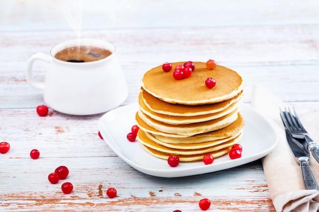 Rano śniadaniowe naleśniki z żurawiną na drewnianym stole i filiżanka kawy