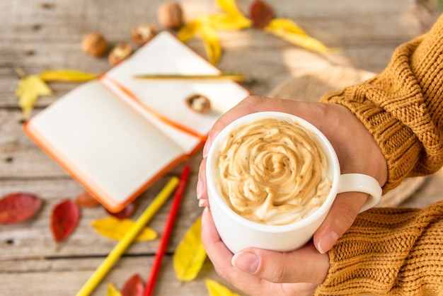 Rano świeżo przygotowane cappuccino i notatki w zeszycie.