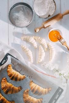 Rano szef kuchni gotuje rogaliki w kuchni, na stole gotowe i surowe rogaliki oraz te same składniki do ich przygotowania
