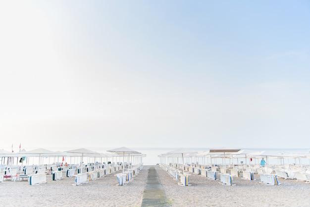 Rano ustawiono wiele rzędów leżaków na plaży.