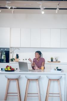 Rano w domu. ciemnoskóra młoda kobieta je śniadanie w domu i ogląda coś na laptopie