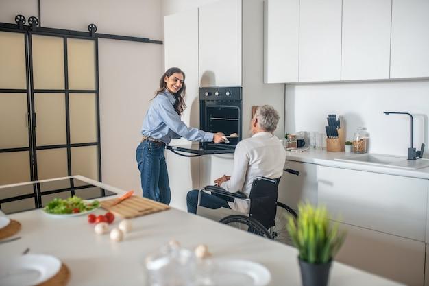 Rano w domu. siwowłosy niepełnosprawny mężczyzna i jego młoda żona w kuchni przygotowują śniadanie