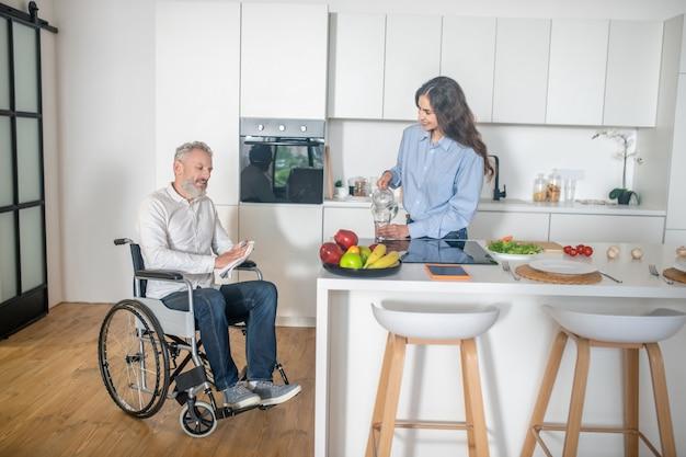 Rano w domu. siwowłosy niepełnosprawny mężczyzna i jego żona w domu przed śniadaniem