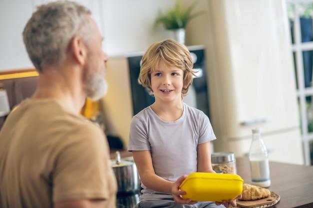 Rano w domu. siwy mężczyzna w beżowej koszulce i jego syn w kuchni w domu