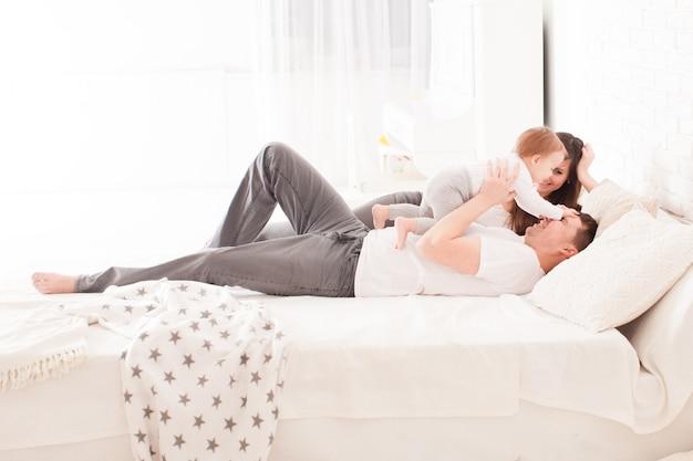 Rano w łóżku, młoda rodzina z małym dzieckiem w sypialni