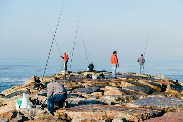 Rano w oceanie atlantyckim w portugalii. grupa nierozpoznawalnych dorosłych mężczyzn połowów. nieznany rybak z wędką. sprzęt wędkarski. skaliste molo.
