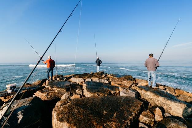 Rano w oceanie atlantyckim w portugalii. grupa nierozpoznawalnych dorosłych mężczyzn połowów.