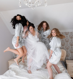 Rano weselnym panna młoda z druhenami radośnie skacze na łóżku i uśmiecha się