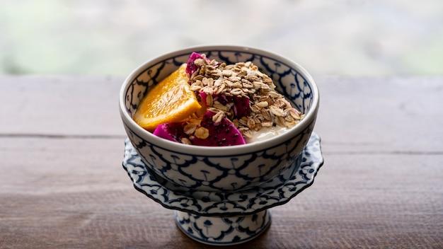Rano zdrowa przekąska śniadaniowa, granola, muesli z jogurtem i owocami tropikalnymi w misce.