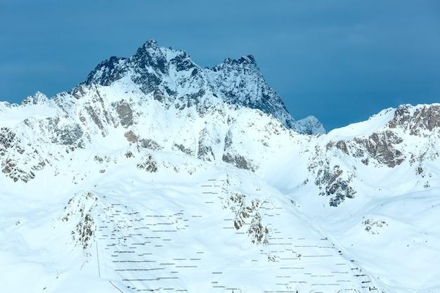 Rano zimowy krajobraz silvretta alps (austria) i ogrodzenie przed zsuwającym się śniegiem na stoku.