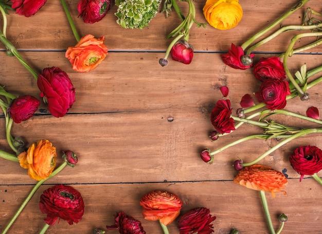 Ranunkulyus bukiet czerwonych kwiatów na tle drewnianych