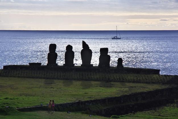 Rapa nui, zachód słońca. statua moai w ahu tahai na wielkanocnej wyspie, chile
