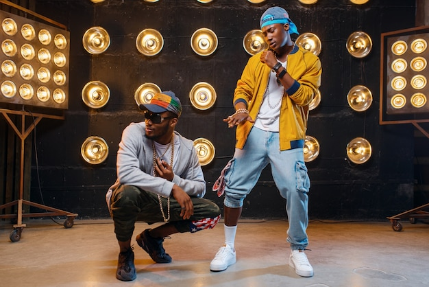 Raperzy w czapkach tańczą na scenie z reflektorami
