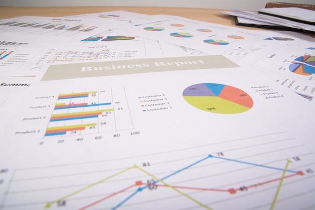 Raport biznesowy. wykresy i wykresy. raporty biznesowe i stos dokumentów. pomysł na biznes.