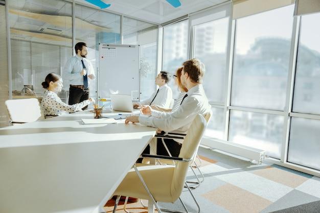 Raport informacyjny. sympatyczni młodzi koledzy siedzący przy stole w sali konferencyjnej i słuchający raportu swojego kolegi stojącego przy tablicy