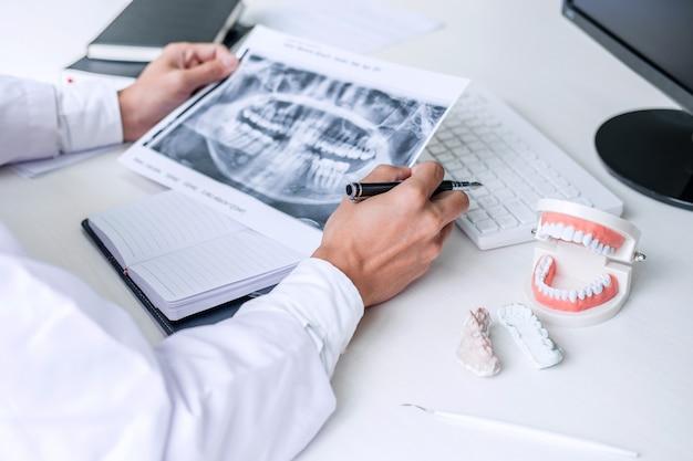 Raport lekarza lub dentysty dotyczący pracy z filmem rentgenowskim zębów, modelem i sprzętem stosowanym w leczeniu