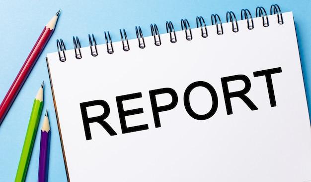 Raport tekstowy na białym notatniku z ołówkami na niebieskim polu