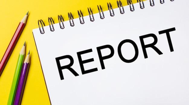 Raport tekstowy na białym notatniku z ołówkami na żółtym tle. pomysł na biznes