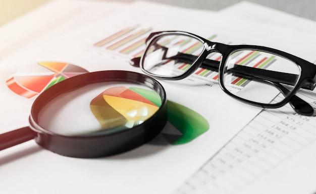 Raporty biznesowe i szkło powiększające z okularami w biurze tabeli. pojęcie analizy danych, planowanie inwestycji, analityka biznesowa.