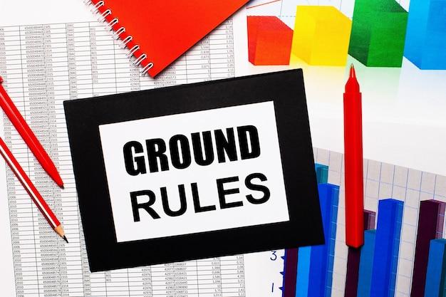 Raporty i wykresy kolorów znajdują się w tabeli. są też czerwone długopisy, ołówek i papier w czarnej ramce z napisem ground rules.