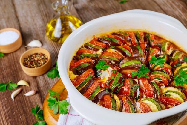 Ratatouille duszone z warzywami z mozzarellą na białej patelni piekarnika.