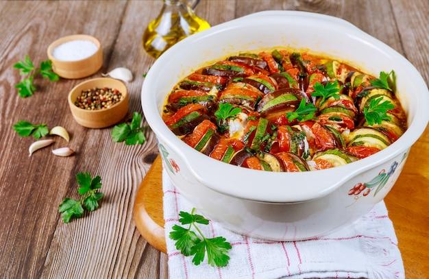 Ratatuj z warzywami gotowanymi z mozzarellą na białej patelni.