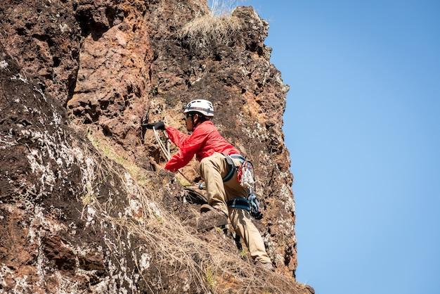 Ratownicy lub wspinacz schodzą w jaskini szybkiej liny w ciemnych jaskiniach
