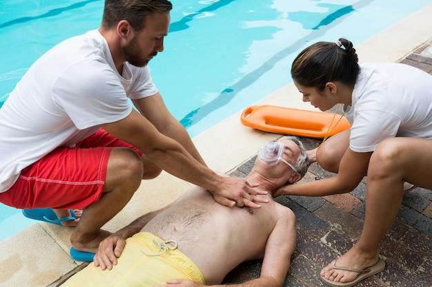 Ratownicy naciskający klatkę piersiową nieprzytomnego starszego mężczyzny przy basenie