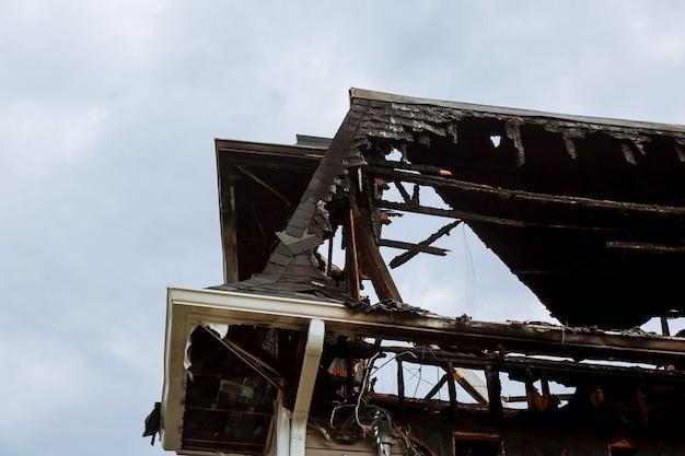 Ratownicy strażacy gasią pożar na dachu. budynek po pożarze.