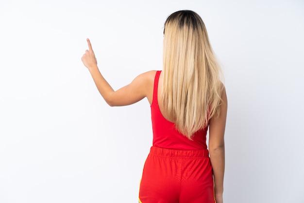 Ratownik kobieta nad odosobnioną biel ścianą wskazuje z powrotem z palcem wskazującym