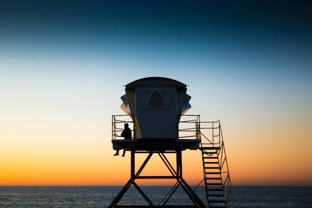 Ratownik na plaży o wieży strażniczej o zachodzie słońca