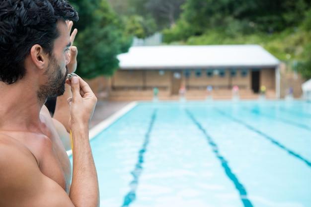 Ratownik patrząc na basen i dmuchanie w gwizdek w słoneczny dzień