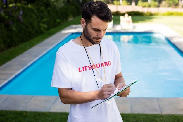 Ratownik pisze w schowku przy basenie w słoneczny dzień