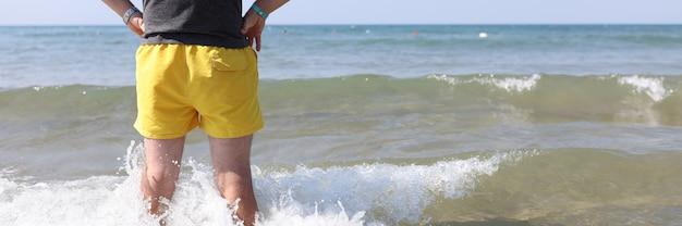 Ratownik w żółtych spodenkach stoi w wodzie morskiej i patrzy w dal