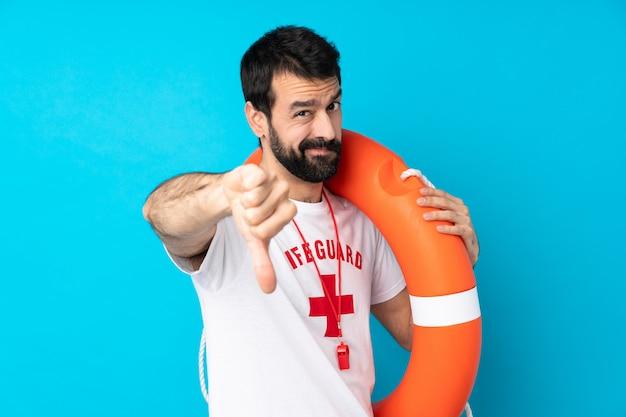 Ratownika mężczyzna nad odosobnioną błękit ścianą pokazuje kciuka puszek z negatywnym wyrażeniem