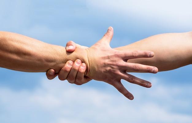 Ratunek, gest pomocy lub ręce. bliska pomocna dłoń. pomocna koncepcja dłoni, wsparcie. przyjazny uścisk dłoni. dwie ręce, uścisk dłoni.
