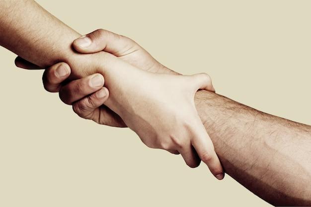 Ratunek, gest pomocy lub ręce. mocne trzymanie. zbliżenie. dwie ręce, pomocna dłoń przyjaciela.