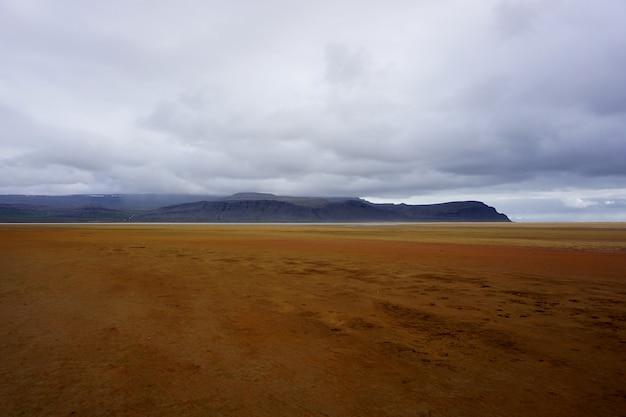 Raudasandur, czyli czerwona piaszczysta plaża na fiordach zachodnich islandii, w pochmurny, deszczowy dzień.
