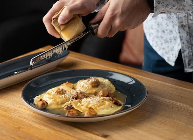 Ravioli z królika z sosem grzybowym i parmezanem z rzepaku na stole w restauracji