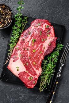 Raw organic chuck eye roll kawałki steków mięsnych. czarne tło. widok z góry.
