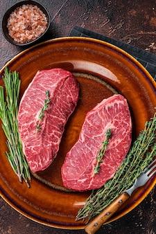 Raw shoulder top blade cut lub australia wagyu ostrygowy stek wołowy. ciemne tło. widok z góry