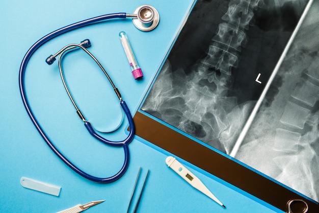 Ð -ray i narzędzia lekarza na niebieskiej powierzchni. pojęcie medyczne