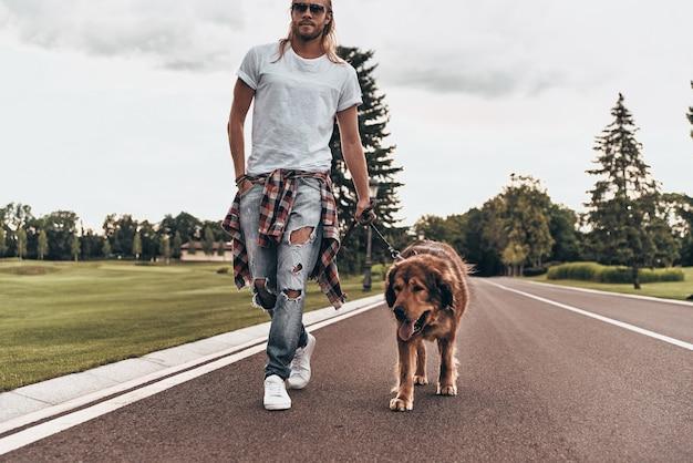 Razem iść naprzód. pełna długość przystojnego młodego mężczyzny spacerującego z psem podczas spędzania czasu na świeżym powietrzu