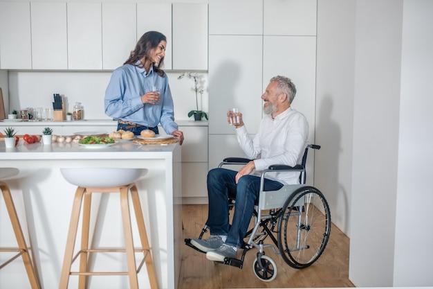 Razem. ładna kobieta dbająca o swojego niepełnosprawnego męża i ładnie się uśmiechająca