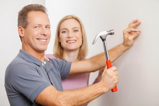 Razem naprawiamy dom. wesoły mężczyzna z siwymi włosami wbijający gwóźdź i uśmiechający się, podczas gdy jego żona stoi blisko niego