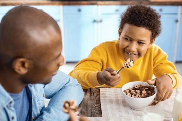 Razem smaczniejsze. radosny chłopiec w wieku przedszkolnym siedzący przy stole obok ojca i uśmiechający się do ojca, jedząc razem z nim płatki śniadaniowe