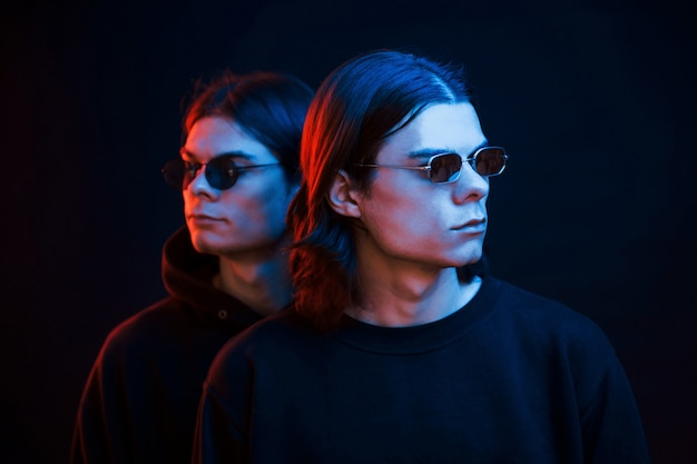 Razem stoimy. portret braci bliźniaków. studio strzałów w ciemnym studio z neonowym światłem